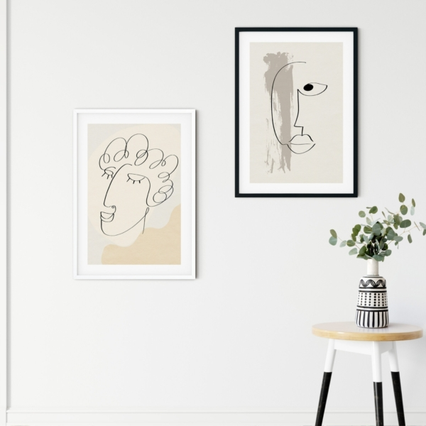 Abstract face #7 and #13 posters in black and white frames on the wall