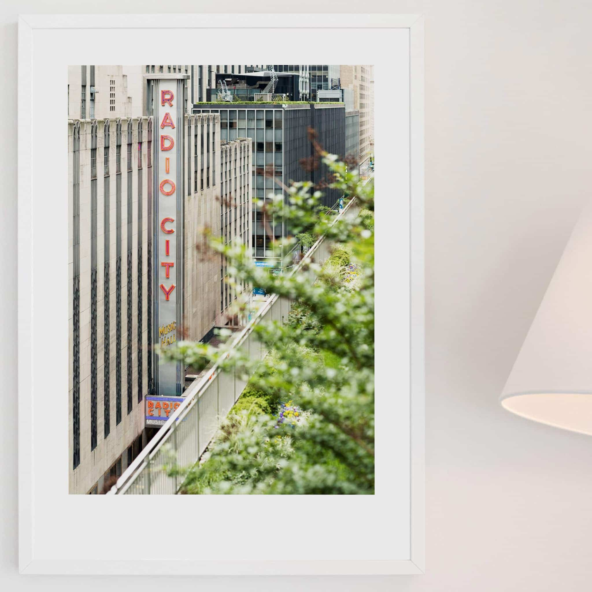 Radio City Music Hall print in white frame on the wall