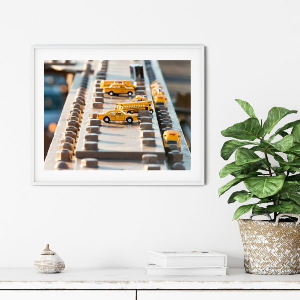 Yellow Toy Cars on Brooklyn Bridge Print in white frame on the wall