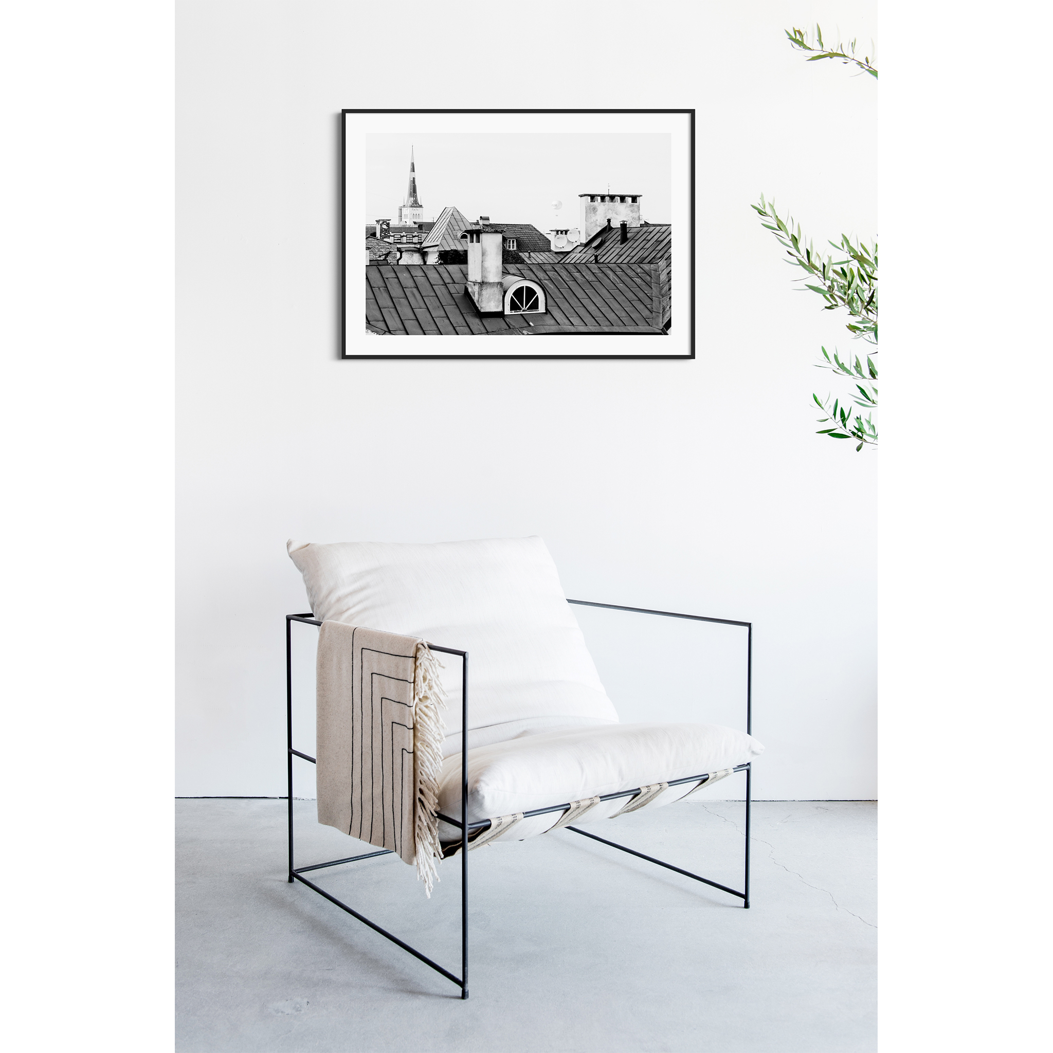 Tallinn Roofs - black and white photography print in the black frame on the wall over the chair